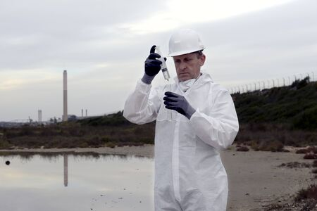 bureta: Trabajador en un traje de protecci�n examinar la contaminaci�n en el agua en la industria. Foto de archivo