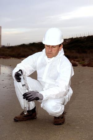 metodo cientifico: Trabajador en una contaminación examinar traje de protección.