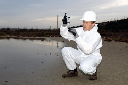 bureta: Trabajador en una contaminación examinar traje de protección.