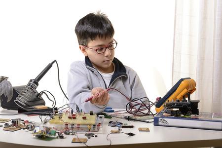Giovane studente compie esperimenti nel campo dell'elettronica e sogni del futuro. Archivio Fotografico