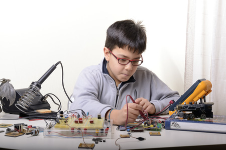 Young student performs experiments in electronics and dreams of the future. Foto de archivo