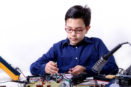 Young student performs experiments in electronics and dreams of the future. photo