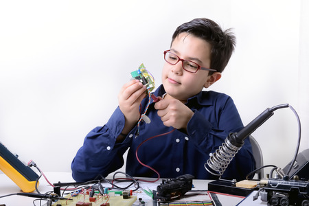 Young student performs experiments in electronics and dreams of the future. 版權商用圖片