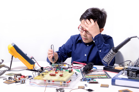 male teenager: Young student performs experiments in electronics and dreams of the future. Stock Photo