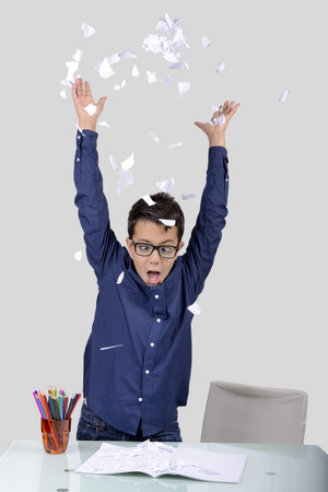 tearing: At home its time to do homework. Grimaces, sadness and difficulties but also jokes. The boy came back to school. Stock Photo