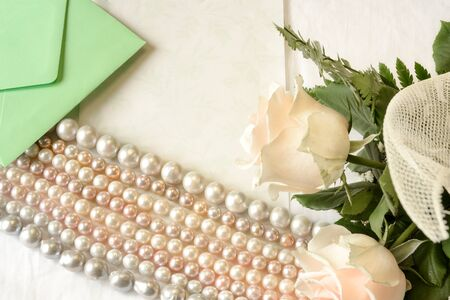 recurrence: Pink roses lying on the table with an empty letter and a pink pearl necklace genuine of Japan. Stock Photo