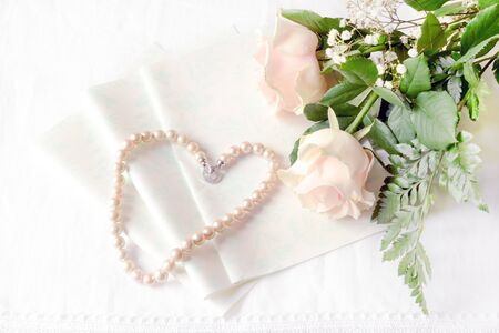 pink pearl: Pink roses lying on the table with an empty letter and a pink pearl necklace genuine of Japan. Stock Photo