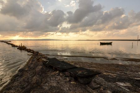 pescador: Atardecer en la laguna, donde los pescadores regresan a la proximidad de la tormenta inminente. Madrugada. Islas del Mediterráneo.