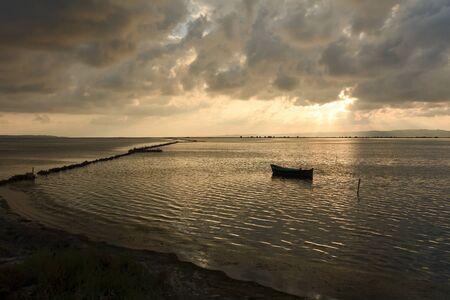 pecheur: Coucher de soleil dans la lagune, où les pêcheurs reviennent à l'approche de la tempête imminente. Este. Îles de la Méditerranée. Banque d'images