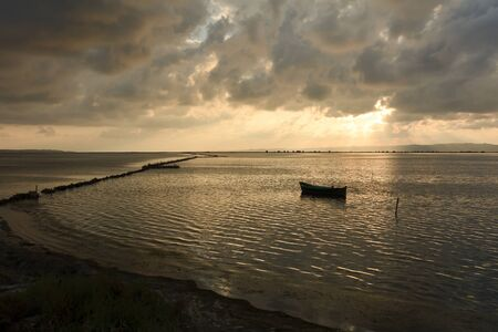 dawning: Sunset in the lagoon, where fishermen return to the approach of the impending storm. Dawning. Mediterranean islands.