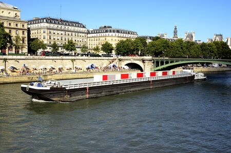 passing over: Barge passing over the Seine, along the banks people spend the summer in Paris.