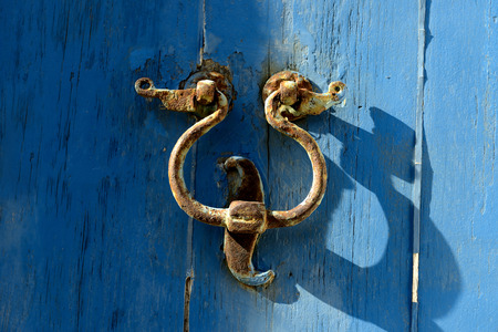 attract attention: Old door knocker on the door with a blue background. A metal instrument to a hinged door and rapped by visitors to attract attention and gain entry.
