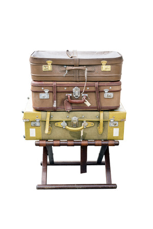 footstool: Old suitcases travel resting on a wooden stool and isolated on white background.