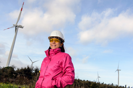 human energy: Engineer woman checking production, with laptops, wind turbines on the site. Stock Photo