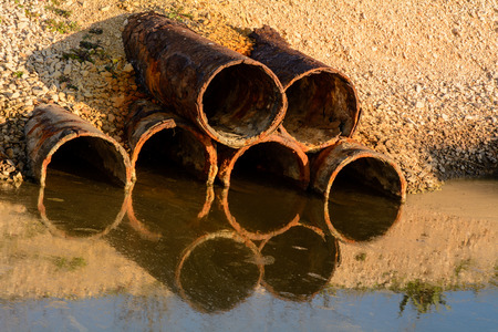 environmental sanitation: Detail of pipes that discharge water and liquids in a river. Stock Photo