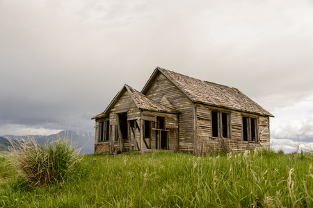 Old abandoned farm in Wyoming, United States. Spring with cloudy sky.