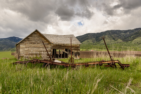 settler: Old abandoned farm in Wyoming, United States. Spring with cloudy sky.
