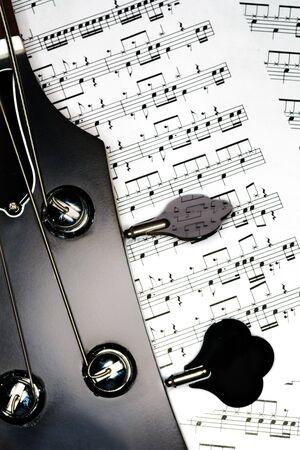 partition musique: Guitare basse �lectrique d�tail t�te, avec un score de musique anonyme dans l'arri�re-plan.