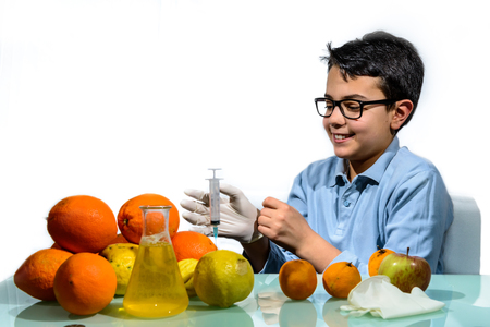 The boy performs experiments with fruit for the lesson of Biology.