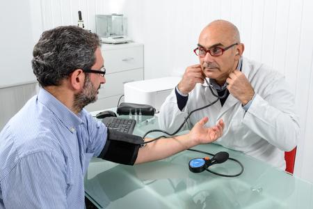 Médico y paciente con medidor de presión arterial en el consultorio del médico.
