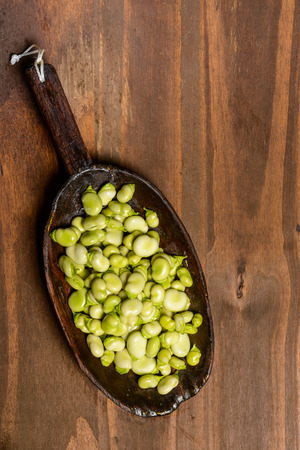 fibber: Fresh green beans seen from above on a rough wood floor brown color. Seasonings of Mediterranean cuisine: olive oil, salt.