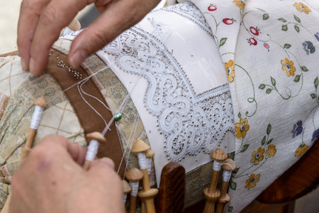 needle laces: Woman hands embroider bobbin lace, lace carefully.