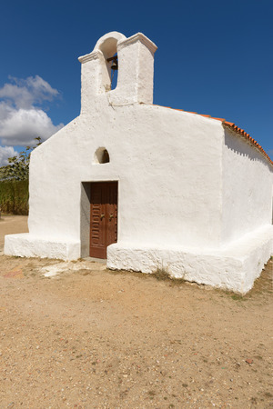 surmounted: Posada, Italy - September 08, 2016: Posada - Church of Saint Lucia, Posada. North Sardinia. Small church with a single nave, the white facade with the entry portal which is surmounted by a large belfry.