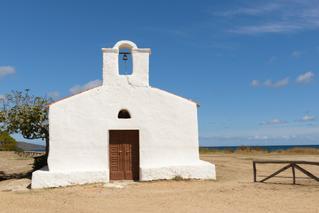 surmounted: Posada - Church of Saint Lucia, Posada. North Sardinia. Small church with a single nave, the white facade with the entry portal which is surmounted by a large belfry. Stock Photo