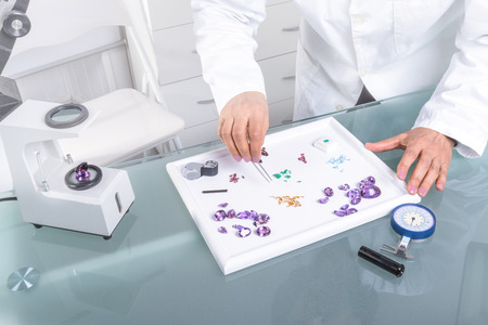 appraising: The Gemologist expertise in her laboratory fix the value of precious stones and  pearls; using optical fibers, Hydrostatic Balance, Polariscope, Refractometer,  Dichroscope. Stock Photo