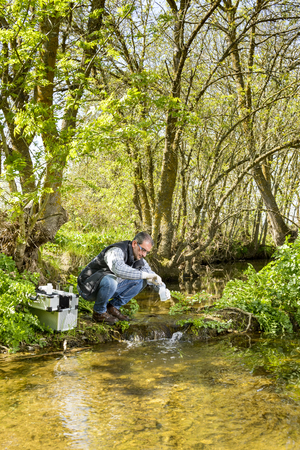 Scientist and biologist hydro-biologist takes water samples for analysis. Foto de archivo