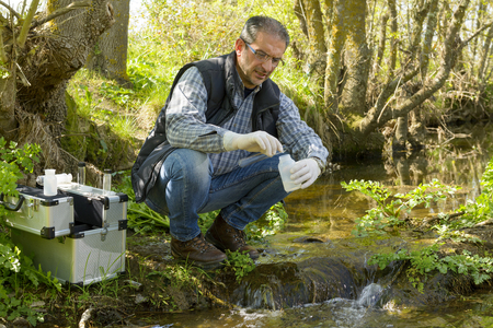 Naukowiec i bio biolog biolog zabiera próbki wody do analizy.