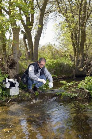 과학자 및 생물 학자 수력 생물 학자는 분석을 위해 물 샘플을 취합니다.