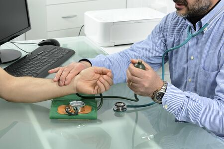 diastolic: Doctor and patient with blood pressure meter isolated in Doctors office. Stock Photo