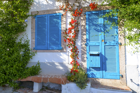 Typical Mediterranean house with white walls and blue fixtures. Boungaville flowers frame the windows. Archivio Fotografico