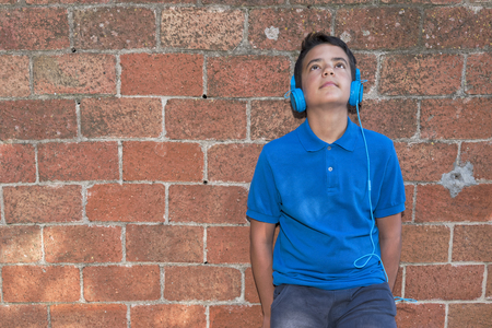 Teenager leaning against a red brick wall, listen to music with headphones.