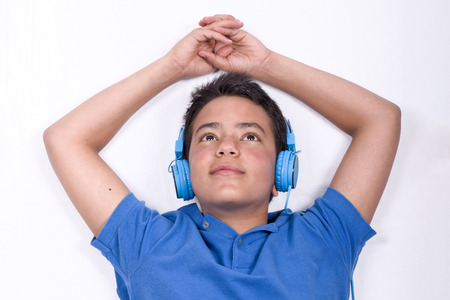 Teenager listening to music with headphones over white background.