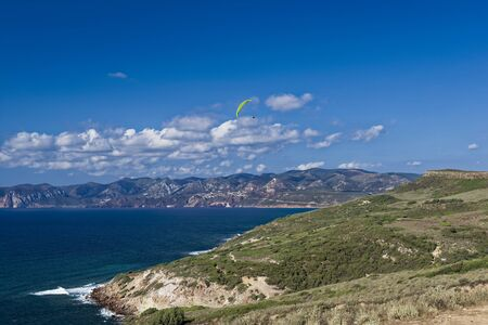 Colorful hang glider in sky over mediterranean blue sea. Sardinia west cost