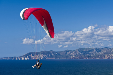 Colorful hang glider in sky over blue sea. Sardinia South West