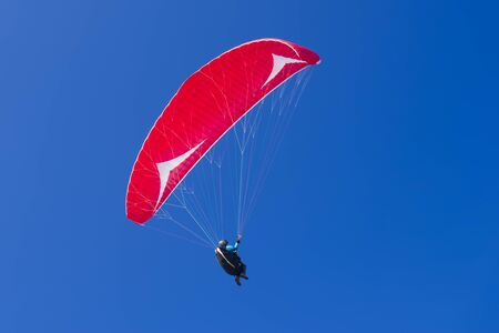 Colorful hang glider in sky over the mediterranean blue sea. Sardinia west coast.