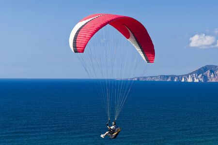 Colorful hang glider in sky over blue sea. Mediterranean South West Sardinia.