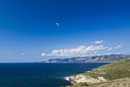 Colorful hang glider in sky over Mediterranean blue sea. Sardinia west coast