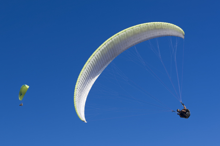 Couple of two paragliding athletes in the blue sky. Archivio Fotografico