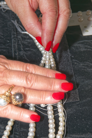 Gemologist  expert assesses the quality of pearls. Womens hands control quality with tools.