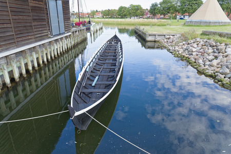 Roskilde, Denmark - August 01, 2015: replica of ancient boat and visitors outside the Vicking Ship Museum