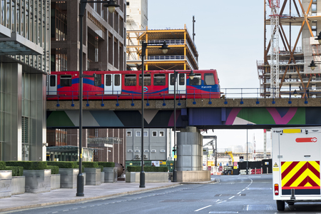 approaches: London, England - August 13, 2017: Overground DLR train approaches Canary Wharf, DLR station in London Stock Exchange district.
