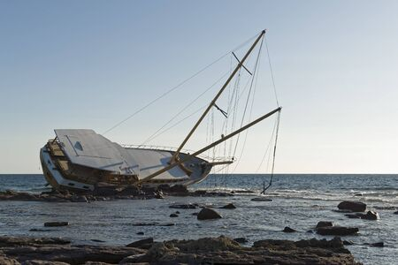 Sailboat, stranded along the coast on the cliff of Sardinia in the Mediterranean Sea. 스톡 콘텐츠