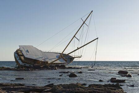 Sailboat, stranded along the coast on the cliff of Sardinia in the Mediterranean Sea. Standard-Bild