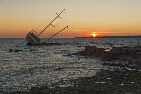 Barca a vela, incagliata lungo la costa sulla scogliera della Sardegna nel Mar Mediterraneo.