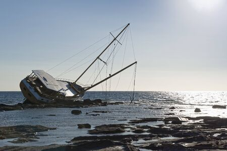 Sailboat, stranded along the coast on the cliff of Sardinia in the Mediterranean Sea. Stock Photo