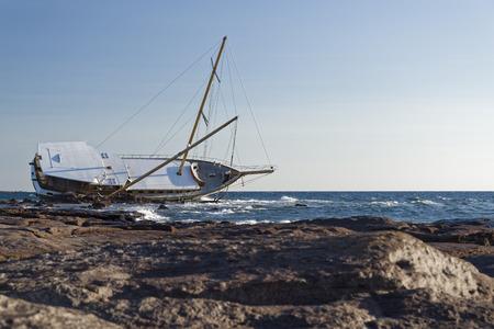Sailboat, stranded along the coast on the cliff of Sardinia in the Mediterranean Sea. Archivio Fotografico